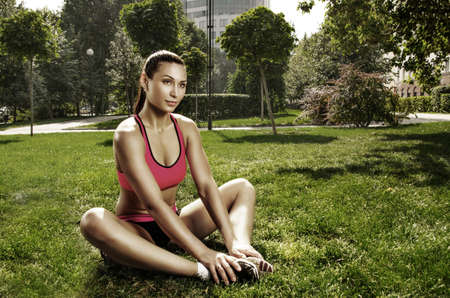 Pretty young caucasian woman training in the park photo
