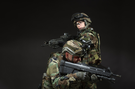 NATO soldier in full gear. Military man and woman over black background. photo