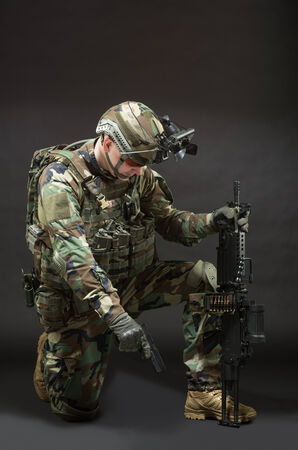 NATO soldier in full gear. Military man over black background. photo