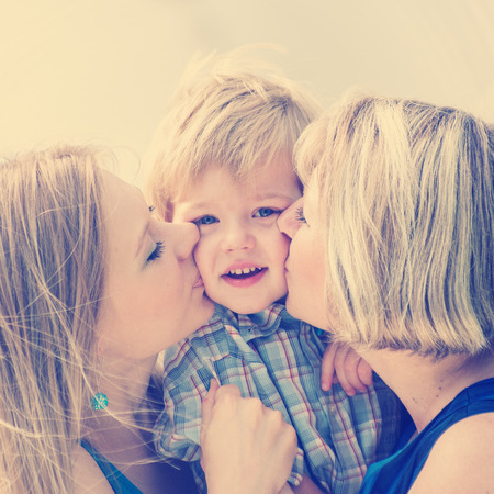 Happy family.Mother, grandmother kissing the little boy. photo