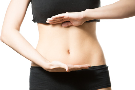 Young woman with hand on her tummy. Part of body. Close-up. Isolated over white background. Stock Photo