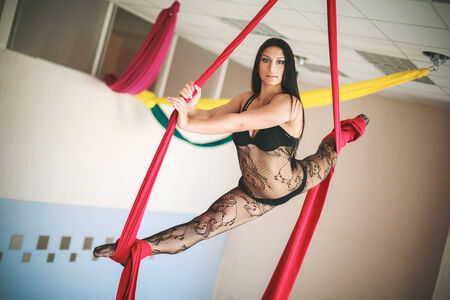 Attractive young caucasian brunette gymnast in lace underwear on the  canvases at the height of the ceiling photo