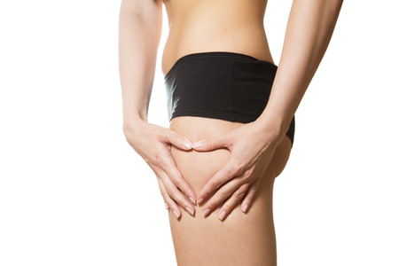 Young woman with hands in heart shape on her hip. Part of body. Close-up. Isolated over white background.