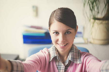 doing business: Portrait of young caucasian business woman in pink vest at her office doing selfie