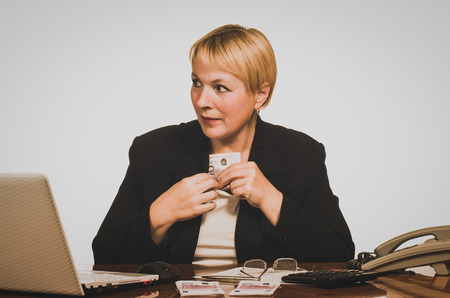 hides: Mature businesswoman hides money. Stock Photo
