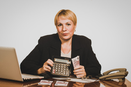 Mature businesswoman showing the sum of money on the calculator. photo