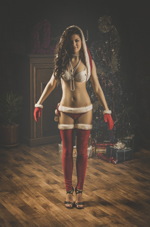 Beautiful xmass brunette as snow maiden near the new year tree and gift boxes photo