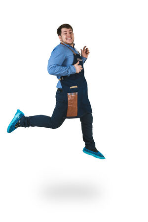 barmen: A shoot of young caucasian men in apron as a barmen. Jumping high. Isolated against white background.