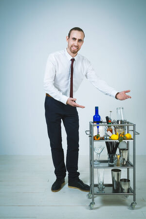 barmen: A shoot of young caucasian men as a barmen offer a cocktail. Stock Photo