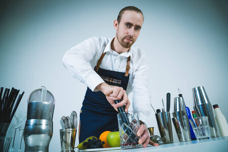 barmen: A shoot of young caucasian men in apron as a barmen standing at the table with dishes, preparing a cocktail. Stock Photo