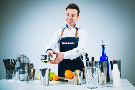 cocktail strainer: A shoot of young caucasian men in apron as a barmen standing at the table with dishes, preparing a cocktail. Stock Photo