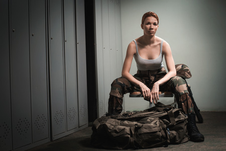 gun room: A shoot of young caucasian beautiful redhead woman sitting on the bench at locker room.