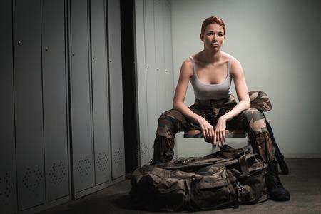 mujer con pistola: Un brote de la mujer cauc�sica hermosa mujer pelirroja sentada en el banco en vestuario.