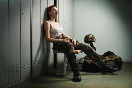 A shoot of young caucasian beautiful redhead woman sitting on the bench at locker room. photo