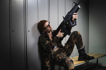 A shoot of young caucasian beautiful redhead woman sitting on the bench at locker room. Сhecking weapon. photo