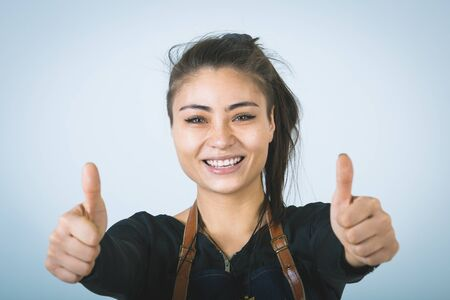 barmen: A shoot of young caucasian woman in apron as a barmen. Showing the sign good, thumbs up.