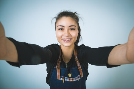 barmen: A shoot of young caucasian woman in apron as a barmen. Doing selfie.Wide Angle.