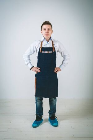 akimbo: A shoot of young caucasian men in apron as a barmen with arms akimbo Isolated against white background. Stock Photo