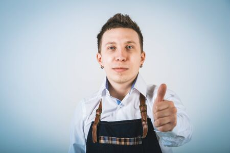 barmen: A shoot of young caucasian men in apron as a barmen. Showing the sign good, thumbs up.