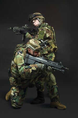 soldier in full gear. Military man and woman over black background. photo