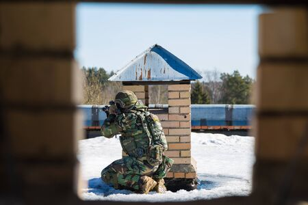A soldier sitting on rhe roof behind air duckt aiming the enemy