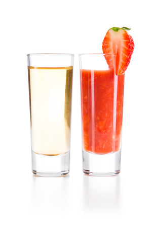 chaser: Tequila Gold with Sangrita and chopped strawberries Chaser. Closeup shoot. Isolated over white background with reflection. Stock Photo
