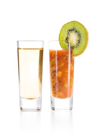 chaser: Tequila Gold with Sangrita and finely chopped kiwi Chaser. Closeup shoot. Isolated over white background with reflection. Stock Photo