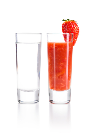 chaser: Tequila Blanco with Sangrita and chopped strawberries Chaser. Closeup shoot. Isolated over white background with reflection. Stock Photo