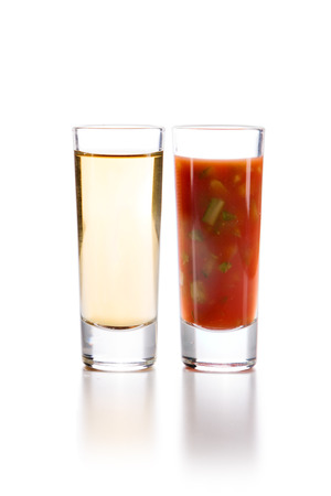 chaser: Tequila Gold with Sangrita and finely chopped celery Chaser. Closeup shoot. Isolated over white background with reflection.