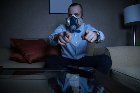 respirator: Handsome young caucasian man in a blue shirt and respirator watching TV pointing directly on you