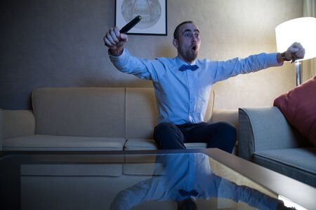 rejoices: Handsome young caucasian man in a blue shirt and bow tie watching TV rejoices goal