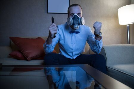 rejoices: Handsome young caucasian man in a blue shirt and respirator watching TV rejoices goal Stock Photo