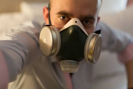 respirator: Handsome young stylish caucasian man in respirator on the bed in the bedroom