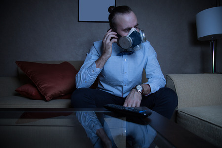 respirator: Handsome young caucasian man in a blue shirt and respirator watching TV, and calling by phone Stock Photo