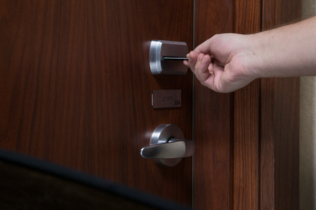 keycard: A hand inserting keycard in the electronic lock.  Closeup shoot.