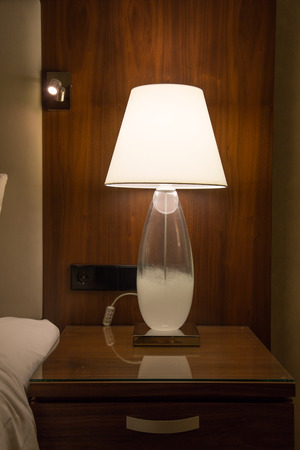 bedside lamp: A lamp on a wooden bedside cabinet