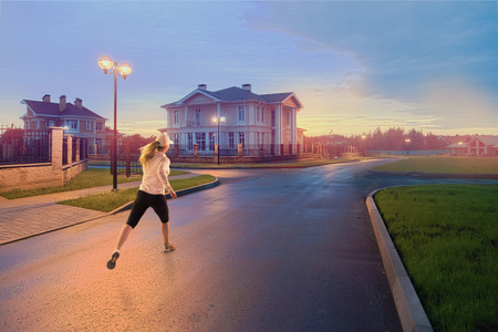 township: Young fitness woman running at township. Stock Photo