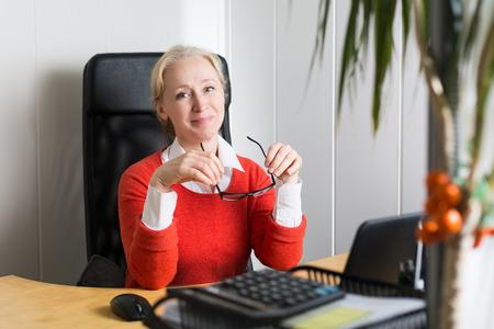Attraente donna caucasica bionda di affari che lavora in ufficio Archivio Fotografico
