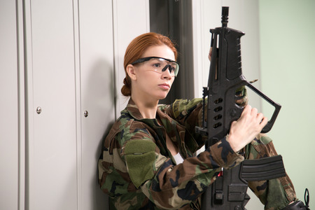A shoot of young caucasian beautiful redhead woman sitting on the bench at locker room. ?hecking weapon. Imagens