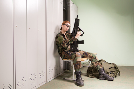 ambry: A shoot of young caucasian beautiful redhead woman sitting on the bench at locker room. ?hecking weapon. Stock Photo