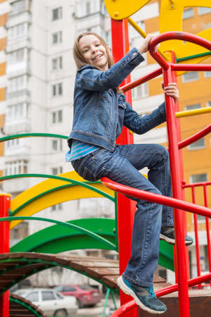 Portrait of beautiful caucasian girl in jeans suit sitting on a playground. photo