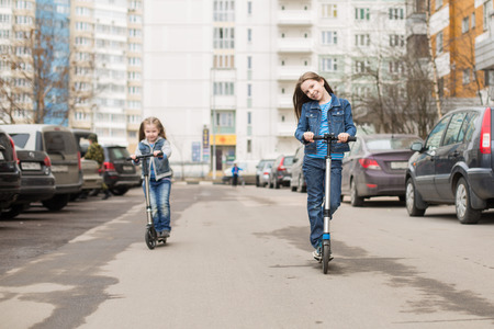 A girl in jeans suit riding a scooter on road parking. photo