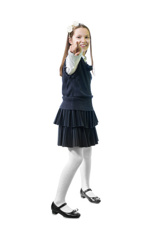 Schoolgirl in uniform against white background.