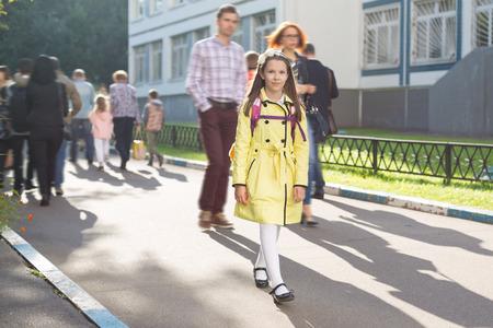 Attractive jeune écolière caucasienne en manteau jaune avec sac à dos Banque d'images - 85256455