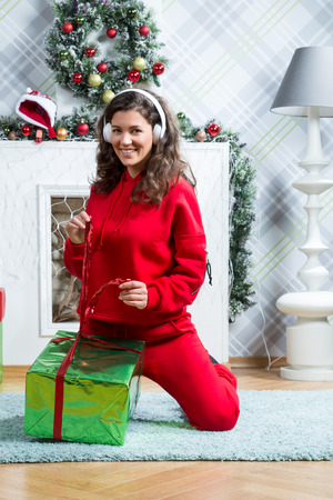 Young Caucasian Beautiful woman with curly hair weared red sport suit at studio with christmas decor Stock Photo