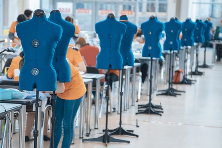 Blurred background with women are engaged in tailoring of tights in a factory