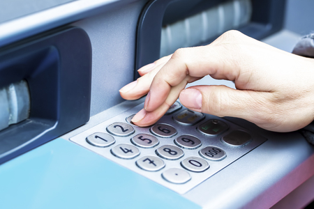 Close up of female hand entering PIN pass code on ATM bank machine keypad