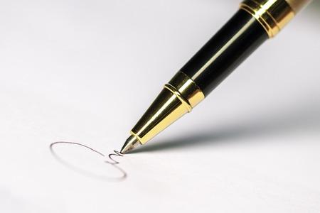 Stift und Unterschrift auf Papierhintergrund