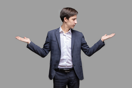 Porträt eines gutaussehenden jungen lächelnden Mannes im Anzug, der darum bittet, zwischen zwei Produkten auf seinen Handflächen zu wählen?