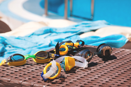 Goggles for swimming near the pool. The concept of swimming lessons for children.